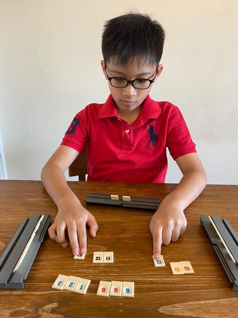 承澤專心玩Rummikub,邊玩邊訓練學習思維